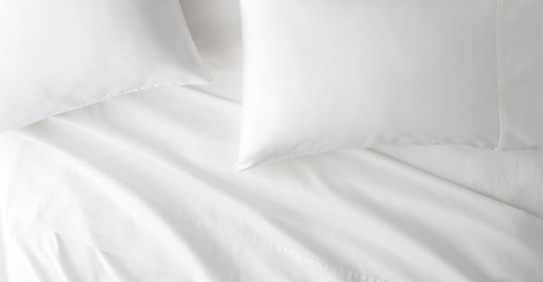 Saatva sheets and pillows on a bed.
